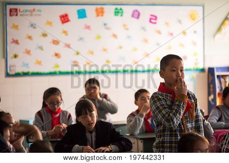 Chengdu, Sichuan Province, China - March 31, 2017: Schoolboy standing in a chinese school
