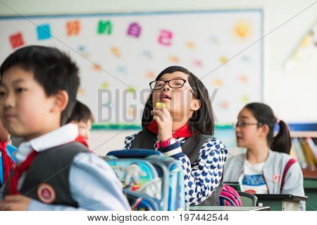 Chengdu, Sichuan Province, China - March 31, 2017: Schoolgirl with a lollipop in a classroom