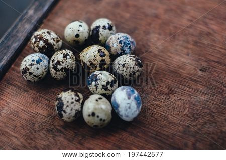 many quail eggs. quail eggs on the brown table. quail eggs on wooden background