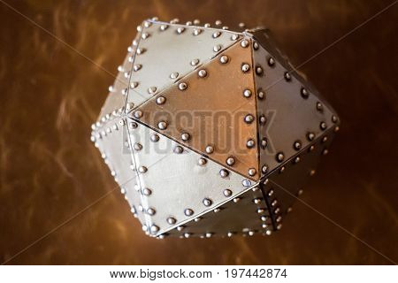 Metal hexagon ball on brown leather background stock photo
