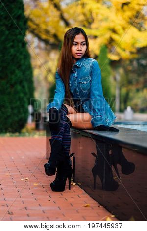 Fashionable young woman wearing blue jeans jacket with the high hills and long stripe knee socks. girl sitting in the park