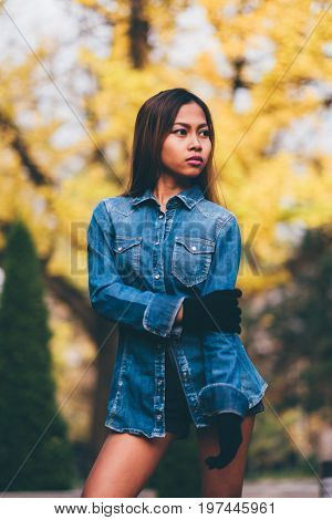 Fashionable young woman wearing blue jeans jacket with the high hills and long stripe knee socks.