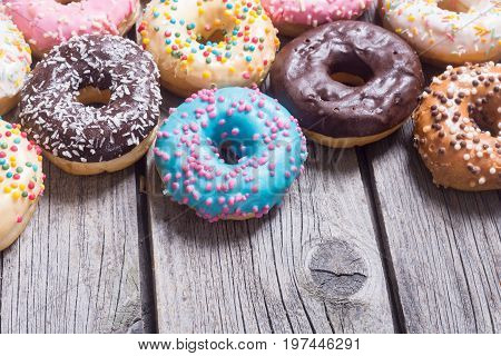 assorted donuts with chocolate frosted pink glazed and sprinkles . with space for text