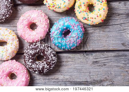 assorted donuts with chocolate frosted pink glazed and sprinkles . Top view with space for text
