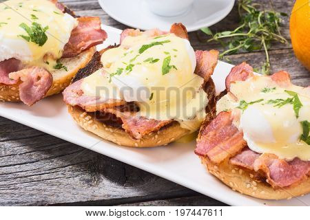 Eggs benedict with bacon on wooden background .