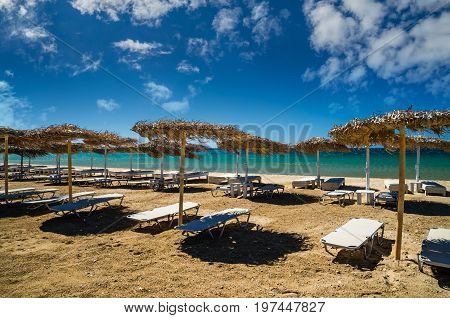 Paros island, Cyclades, Greece. Straw umbrellas and beach loungers on Golden Beach.