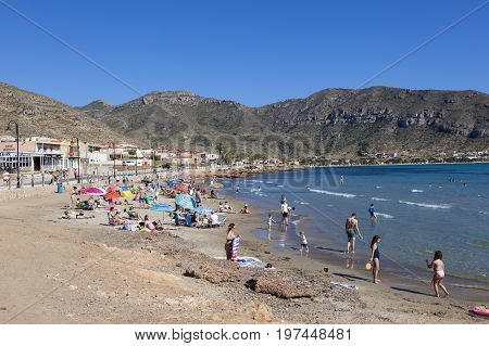 Azohia Spain - May 14 2017: People relaxing on the small beach in town La Azohia. Province of Murcia southern Spain