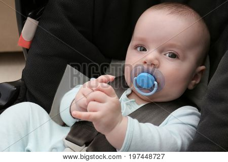 Cute baby boy with pacifier sitting in safety car seat