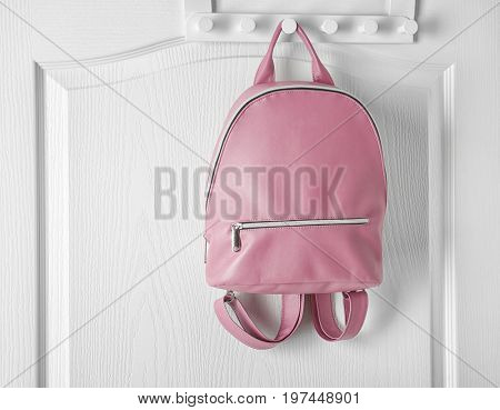 Hanger with leather backpack on door