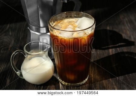 Glass with cold brew coffee and milk in small jug on wooden table