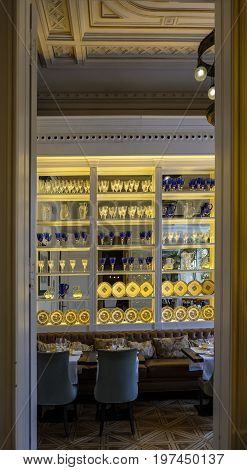 BARCELONA SPAIN - 8 JUNE 2017: Looking through doorway to beautiful dining room of luxury Cotton House Hotel in Barcelona with comfortable seating and glass shelves of plates and glassware