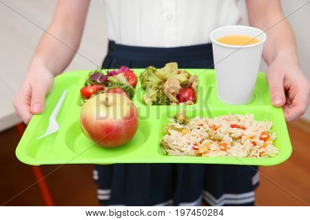 Girl holding tray with delicious food in school canteen, closeup
