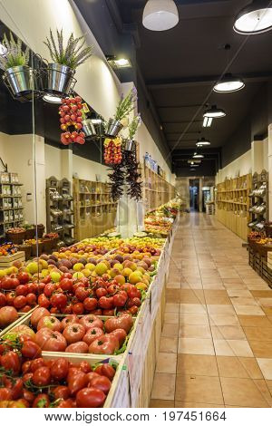 Display of colorful fruit and vegetables in long narrow shop