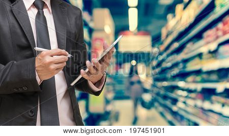 Businessman using the tablet on Abstract blurred photo of store in department store bokeh background business shopping concept