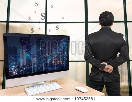 the computer on the wood table with trading graph at the screen in front of the glass window over on the trading graph over the blurred photo of cityscapeBack side of Businessman