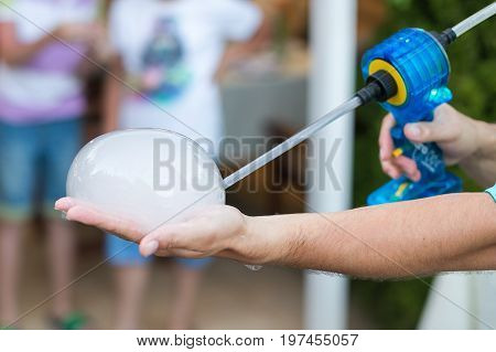 magic show performance, holiday celebration and miracle concept - male illusionist inflates bubble with smoke gun on a palm, soap bubbles concert, compact fog machine, selective focus