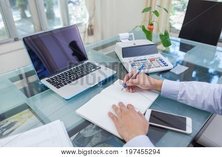 Business Man Writing On Notebook During Working At Home
