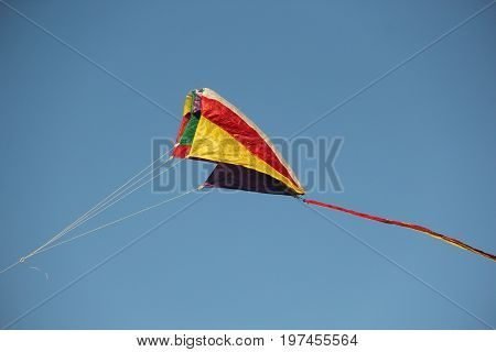 A multi colored kite flying in blue skies