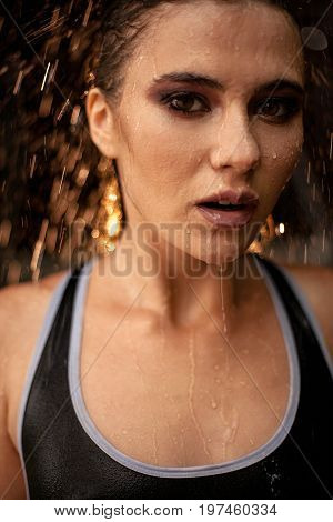 Portrait of wet girl in rain with drops and jets of water flowing down her face. Backlight.