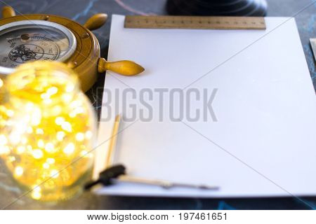 Barometer on a background of a white sheet of paper with lights in a glass jar