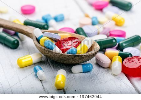 Full wooden spoon of tablets. Pharmacy background on a white table. Tablets on a white background. Pills. Medicine and healthy. Close up of capsules. Differend kind of pills