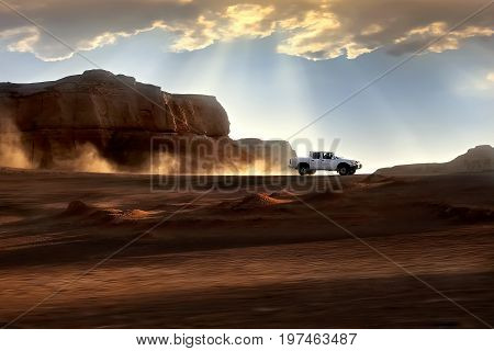 The car rides with great speed through the desert against the background of the setting sun. Beautiful rays of light and clouds. Iran. Kerman. Dasht-e Lut Desert.