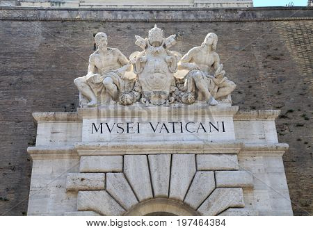 Main entrance to the Vatican Museum with sign and sculptures in Rome, Italy