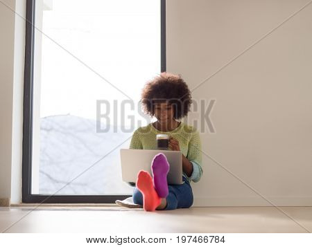 Young african american woman smiling sitting on the floor near bright window while looking at open laptop computer and holding mug at home