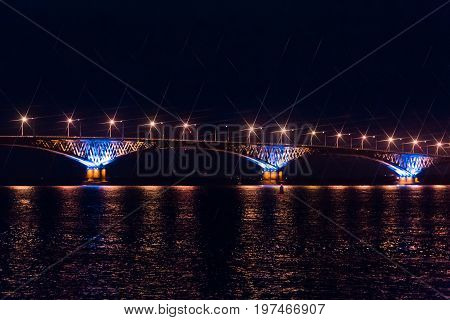 Road bridge across the Volga river between the cities of Saratov and Engels, Russia. Night or evening landscape. Golden street lights. The reflection in the water