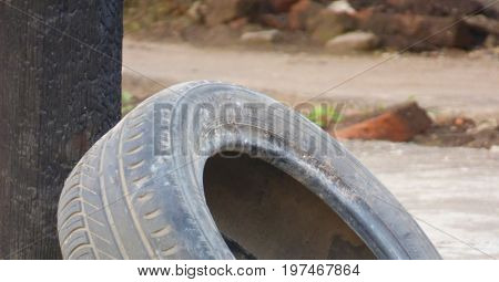 Abandoned tire. Car tire leaning on a post. Obsolete pneumatic