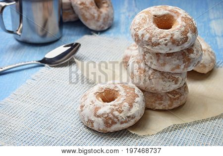 Cup of coffee with biscuit cookies and spoon. Homemade biscuit. Cookies in glaze on white linen napkin on wooden table. Coffee break breakfast.