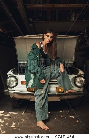 Girl worker in dirty green overalls stands in workshop near opened capote of retro car.