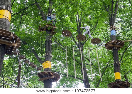 Children a boy and a girl in climbing gear during training a rope town in the trees an extreme rope maze with trees