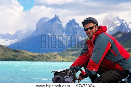 Man on a bicycle on the road leading to the impressive Cuernos del Paine peaks in Torres del Paine National Park, Chile, South America