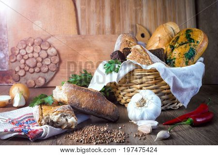 Fresh bread, buckwheat bread, garlic bread, French baguette in a basket, on a table, with vegetables