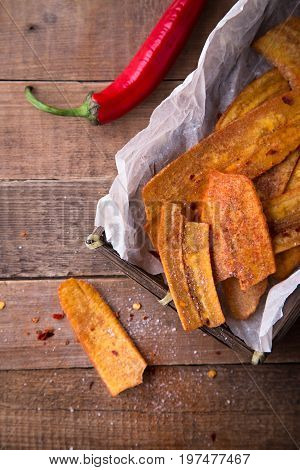 Fried thinly sliced banana chips with chili pepper and lemon, Mexican fast food