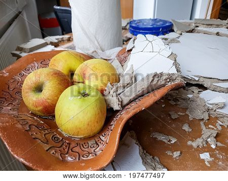Fruit basket filled with panels after ceiling collapsed. Destroyed kitchen.