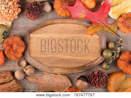 Blank wood plaque surrounded by colorful autumn objects