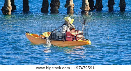 Fisherman with fishing gear paddling a Kayak in blue water near a jetty. Coffs Harbour New South Wales Australia.