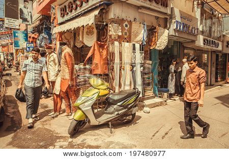 BANGALORE, INDIA - FEB 14, 2017: People making shopping on market indian street full of stores on February 14, 2017. With population 8.52 million Bangalore is 3-rd most populous indian city