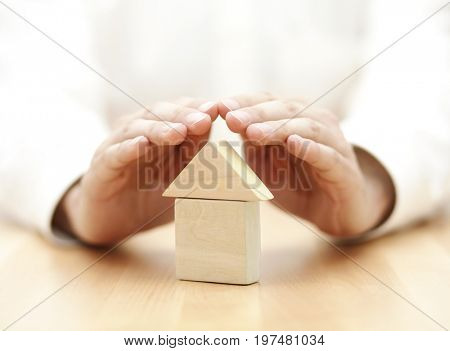 Wooden toy house protected by hands