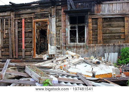 War destroyed, burned down wooden house, charred walls, burnt roof, black ceilings