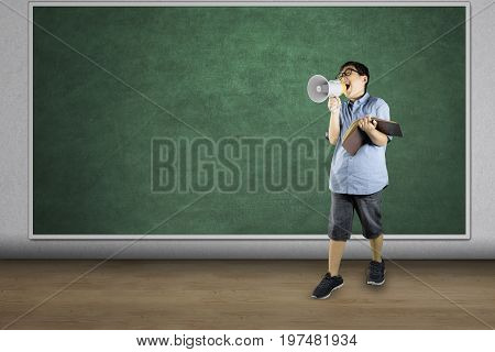 Full length of boy student speaking on megaphone while holding a book and standing in the class
