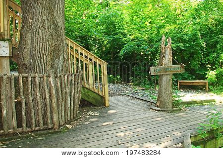 Sign post and steps to Tom's treehouse as seen from a boardwalk walking trail, through the lush woods in the Fontenelle Forest Nature Center in Bellevue, Nebraska near Omaha.