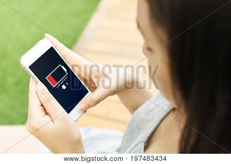 Asian young woman hand holding mobile phone with low battery on screen