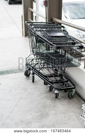 Row Of Black Shopping Cart With Black Handle Lined Up On Cement Floor
