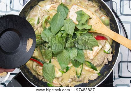 Chef putting Thai basil for cooking green curry / cooking green curry concept