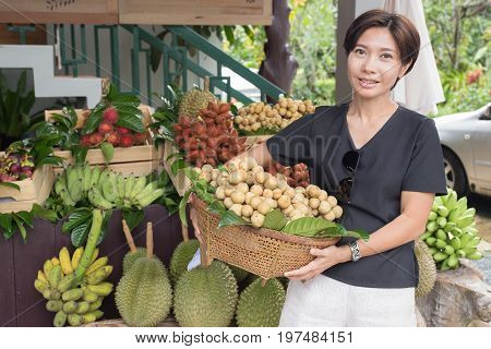 Asian woman with tropical fruit basket in the market