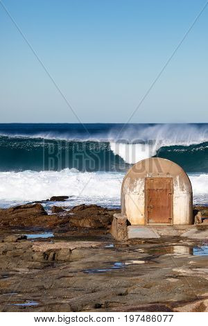 Newcastle Ausralia - Large surf breaking beyond the pumphouse at the Cowrie Hole - Newcastle Australia. This pumphouse is a local landmark and delivers water to the adjacent Newcastle ocean baths.