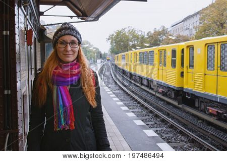 Young hipster woman in glasses and in warmclothes in train station platform, portrait